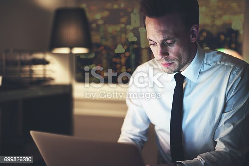 istock Businessman working on laptop at night 699826280
