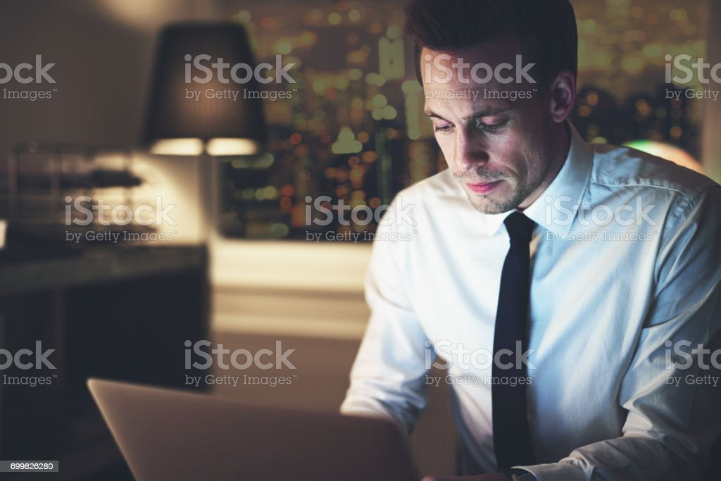 Businessman working on laptop at night stock photo