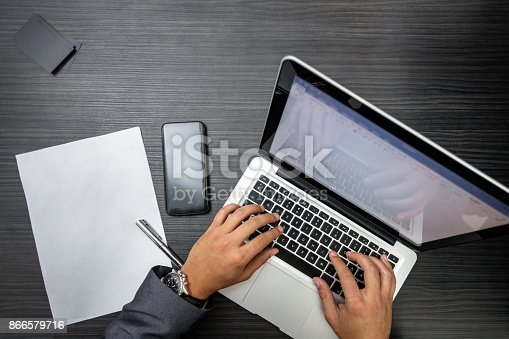 879813798istockphoto Businessman working on laptop at the office 866579716