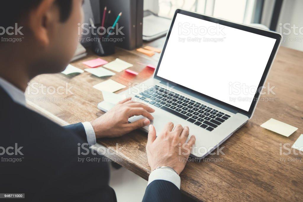 Geschäftsmann, arbeiten auf Laptop-Computer mit leeren weißen Bildschirm an seinem Schreibtisch – Foto