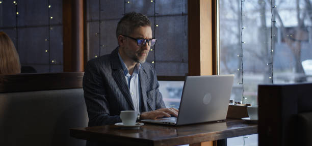 Businessman working on laptop in cafe Medium shot of businessman drinking coffee and working on laptop in cafe letterbox format stock pictures, royalty-free photos & images
