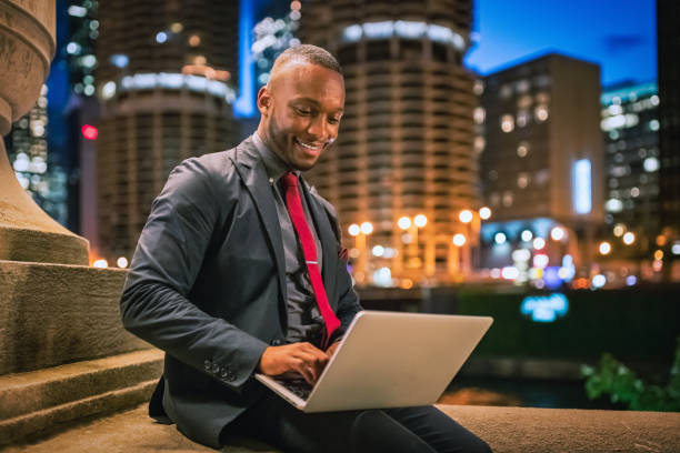 Businessman working on Laptop in Downtown Chicago at Night