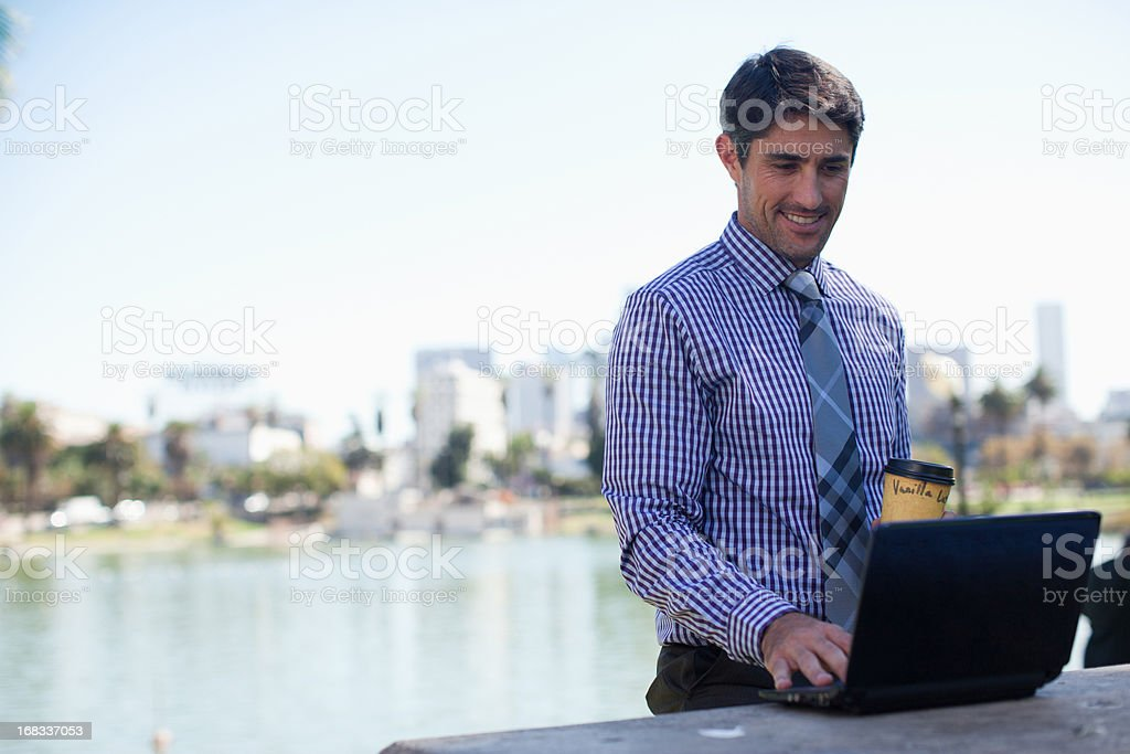 Businessman working on laptop in park royalty-free stock photo
