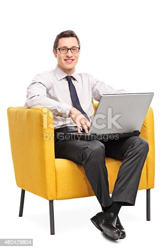 944992706 istock photo Businessman working on laptop seated in an armchair 482429804