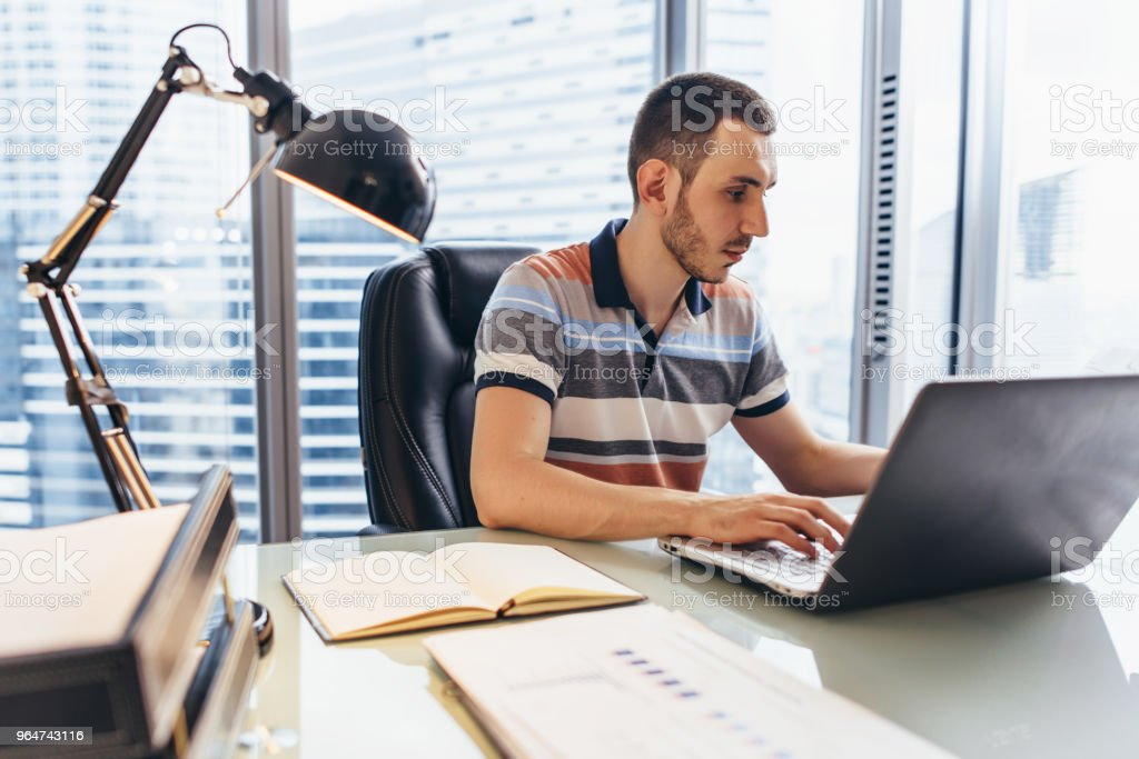 Businessman working on laptop using internet searching for information sitting at desk in office royalty-free stock photo