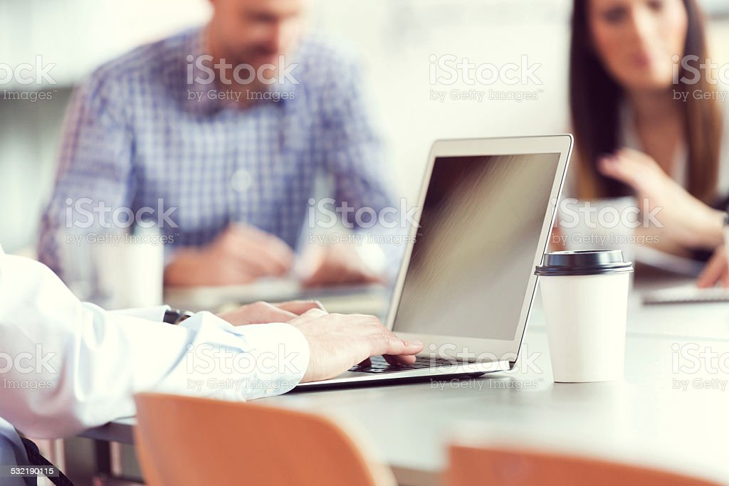 Businessman working on latop in an office Business people having meeting in board room. Focus on businessman working on laptop. 2015 Stock Photo