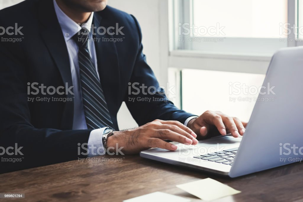 Businessman working on notebook computer in the office stock photo