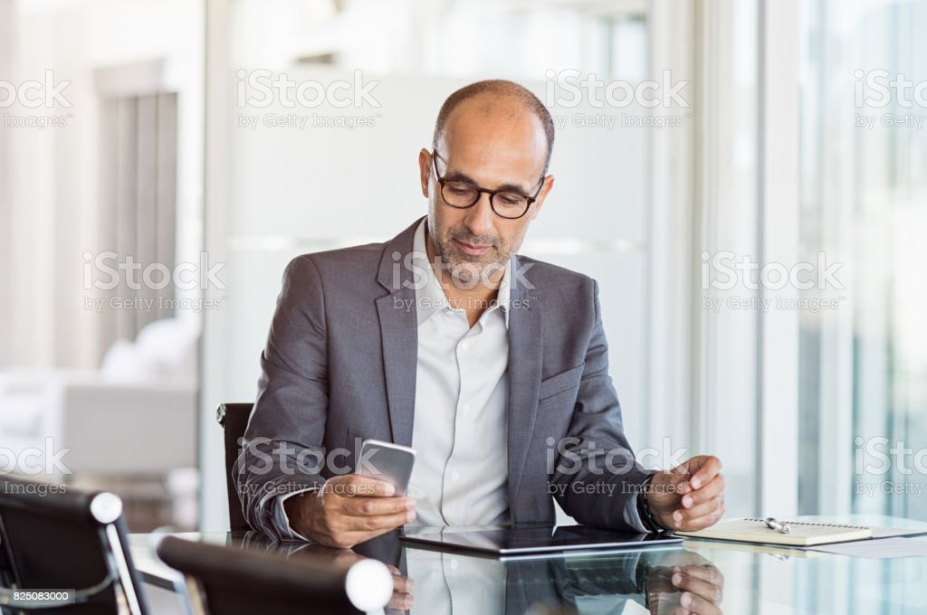 Businessman working on phone Mature business man in formal clothing wearing spectacles using mobile phone. Serious businessman using smartphone and digital tablet at work. Manager in suit using cellphone in a modern office. 40-49 Years Stock Photo