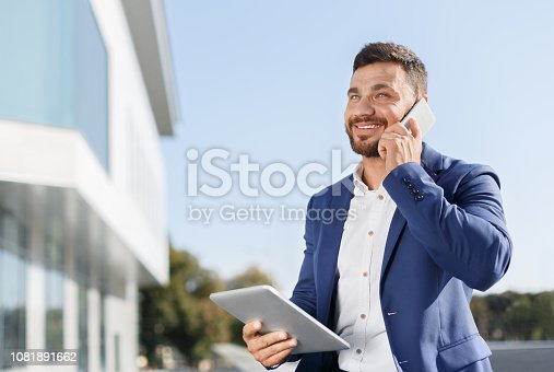 istock Businessman working on tablet and talking on phone 1081891662