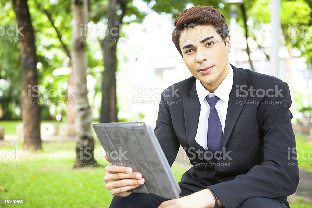 Businessman working outdoors with digital tablet PC at the park. royalty-free stock photo