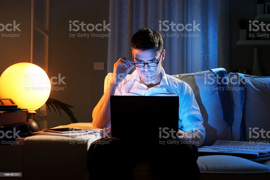 Businessman working overtime at home until late stock photo