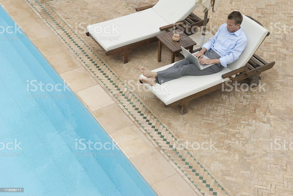 Businessman Working Poolside Outdoors with Laptop royalty-free stock photo