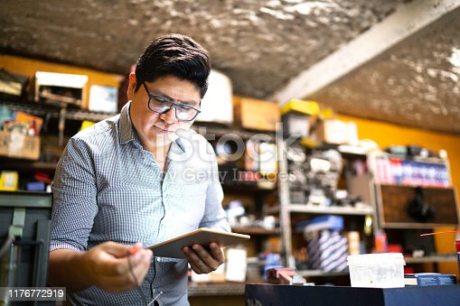 1137474295 istock photo Businessman working using tablet in a auto repair shop 1176772919