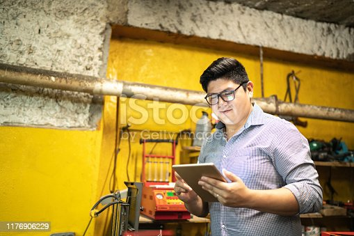 1137474295 istock photo Businessman working using tablet in a auto repair shop 1176906229