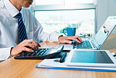 Businessman working with digital tablet and laptop in office room.