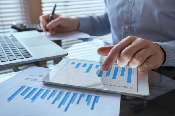 geschäftsmann, der mit finanzberichtsdiagrammen, business analytics und kpi arbeitet - geschäftsstrategie stock-fotos und bilder