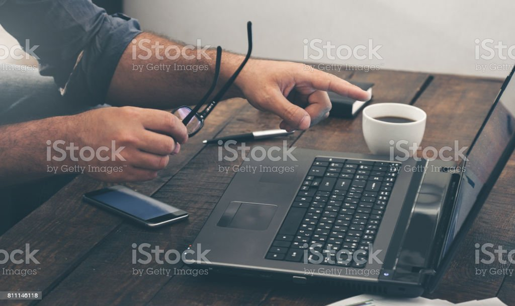 Businessman working with laptop at home office on wooden table stock photo
