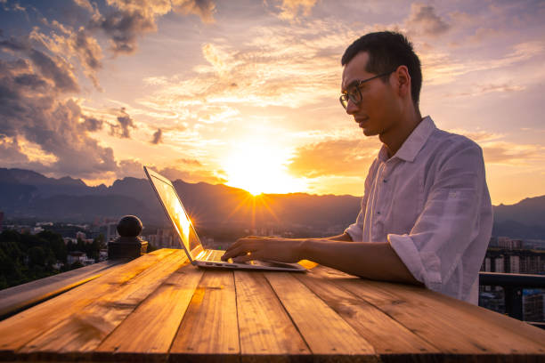 Businessman working with laptop at sunset stock photo