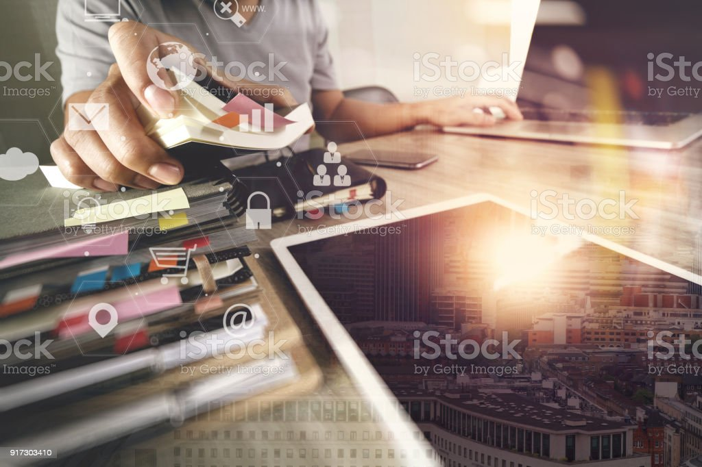 businessman working with laptop computer and document on wooden desk in modern office with virtual icons interface stock photo