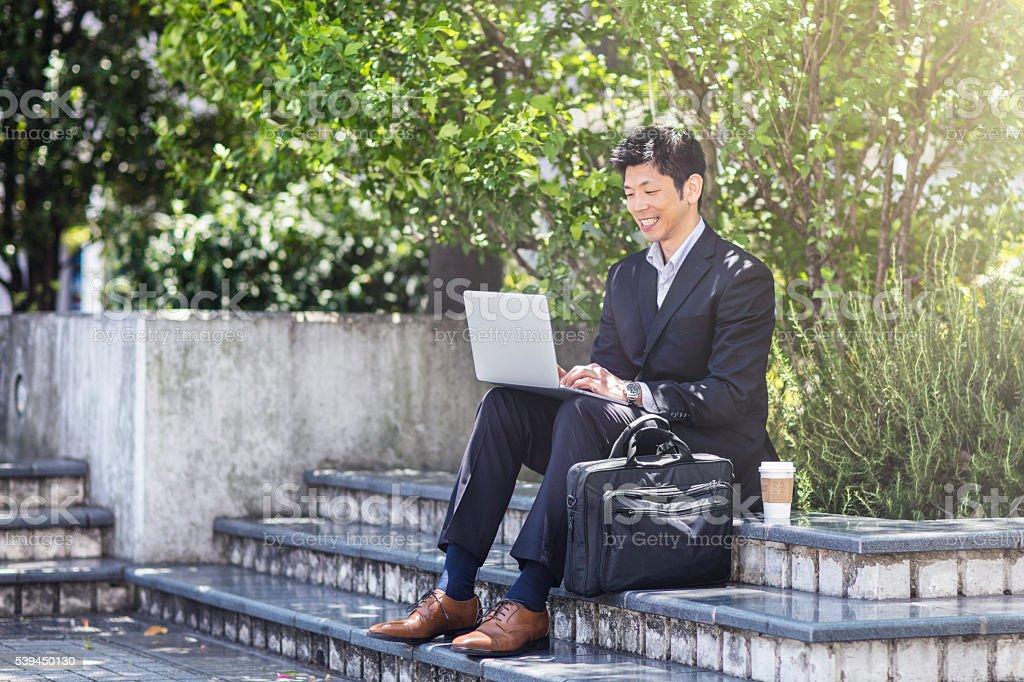 Uomo d'affari lavorando con computer portatile su edificio a pochi passi - foto stock