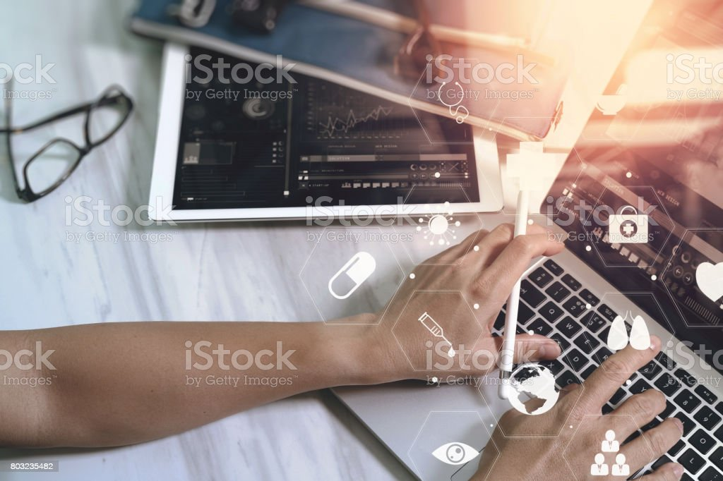 businessman working with smart phone and laptop computer on wooden desk in modern office with virtual icons interface stock photo