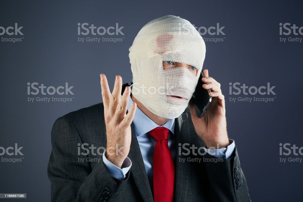 A formally dressed businessman, his head completely wrapped in...