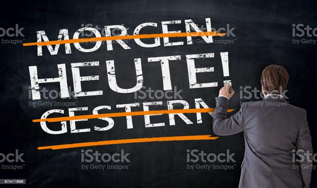 Businessman writes in german Today, Yesterday, Tomorrow on blackboard Concept stock photo