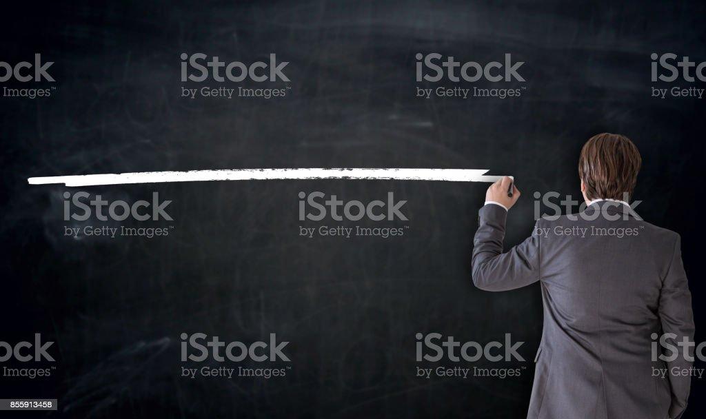 Businessman writes template on blackboard concept stock photo
