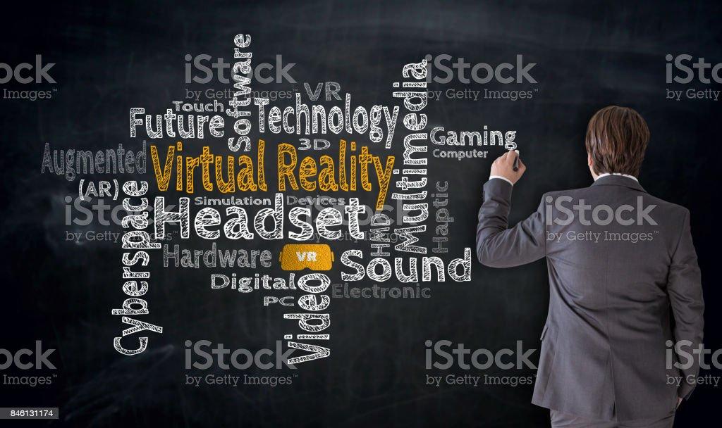 Businessman writes Virtual Reality Cloud on blackboard concept stock photo