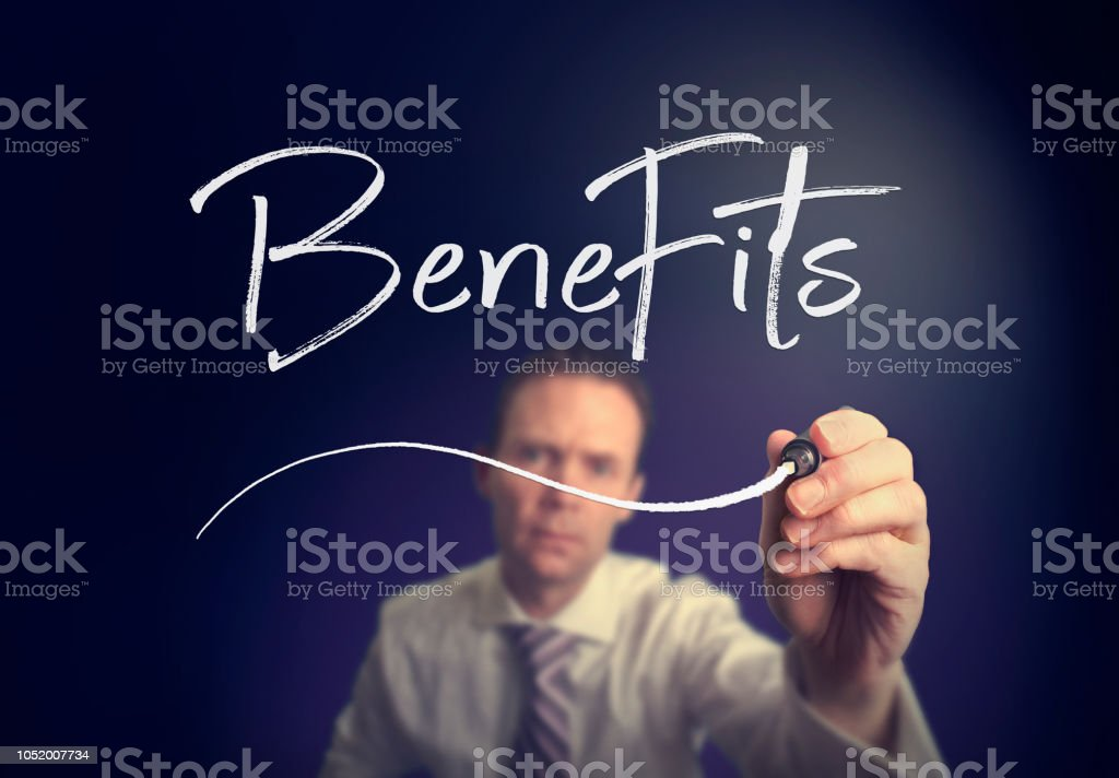 A businessman writing a Benefits concept with a white pen stock photo