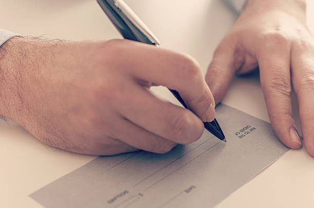 Businessman writing a payment check stock photo