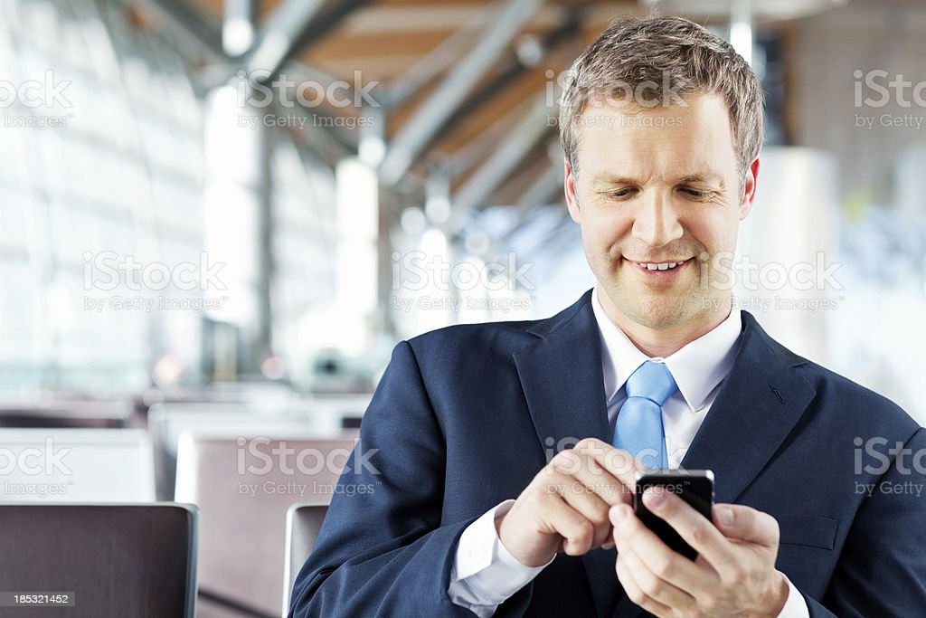 Businessman Writing a Text Message on His Phone At Airport royalty-free stock photo
