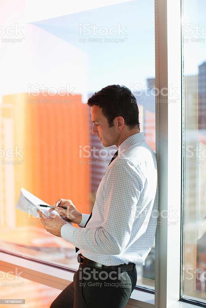 Businessman writing at window in office royalty-free stock photo