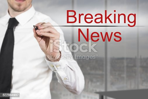 istock businessman writing breaking news in the air 522964937