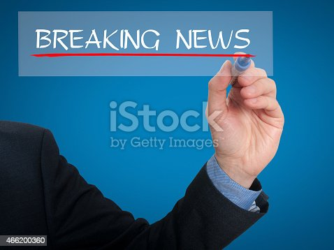 istock Businessman writing breaking news in the air - Stock Image 466200360