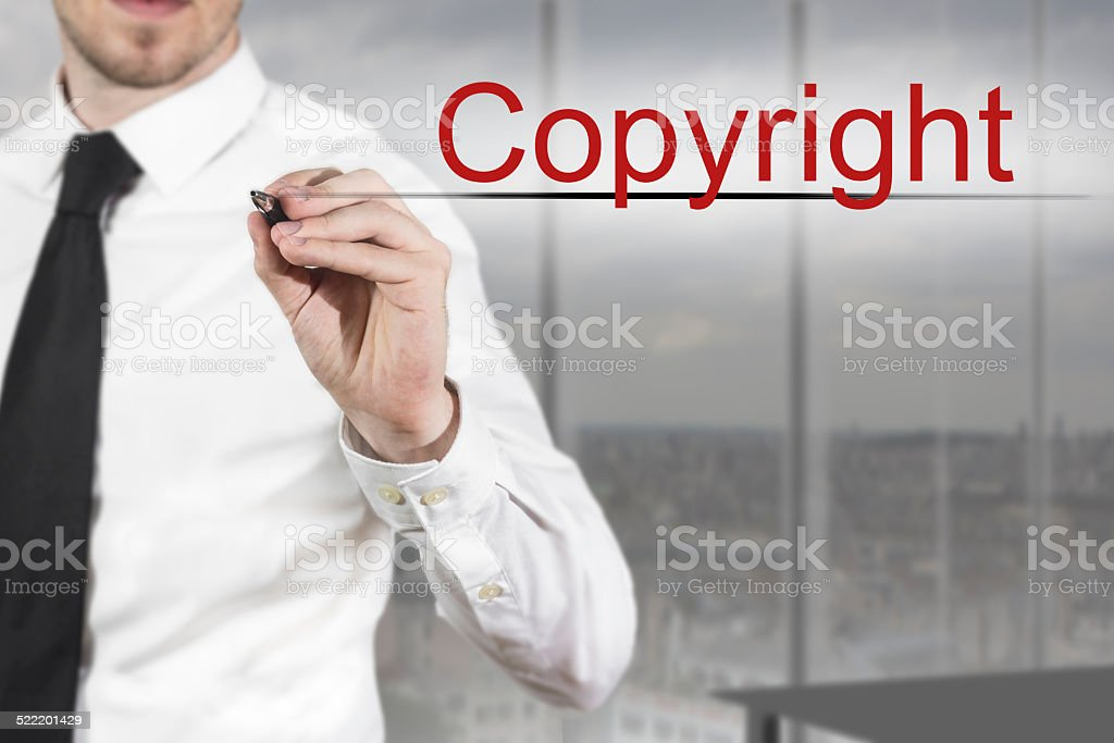 businessman writing copyright in the air stock photo
