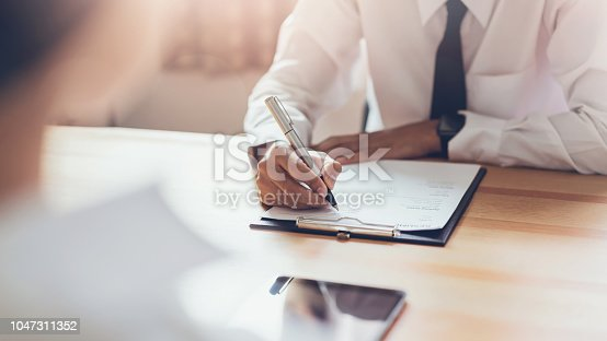 istock Businessman writing form submit resume employer to review job application. Concept presents ability for the company to agree with position of job. 1047311352