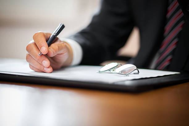 Businessman writing in a document stock photo