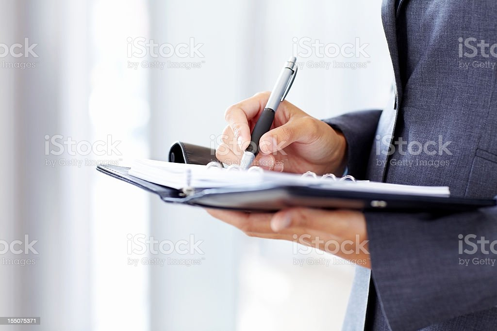 Businessman Writing in a Planner stock photo