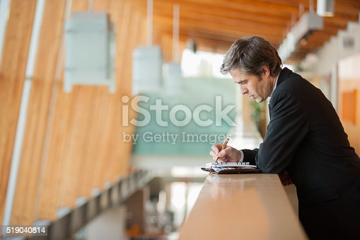 530281733istockphoto Businessman writing in a weekly planner 519040814
