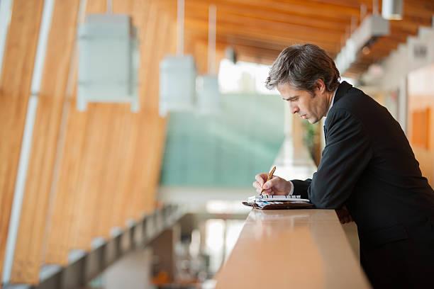 businessman writing in a weekly planner - technique photographique photos et images de collection