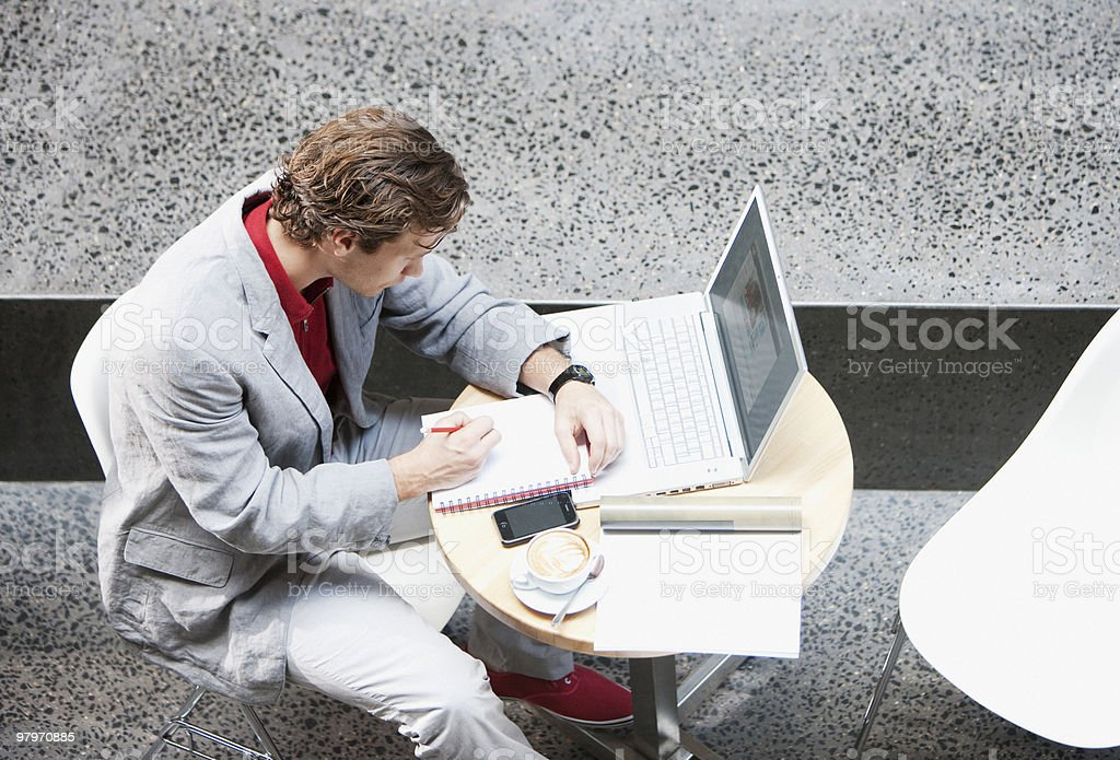 Businessman writing in notepad at table with laptop and coffee royalty-free stock photo