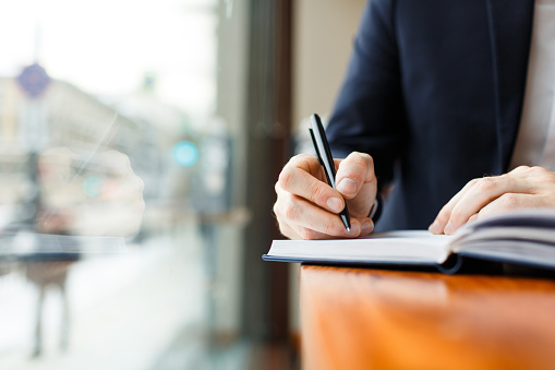 Closeup shot of unrecognizable businessman wearing formal suit making notes in planner scheduling for day