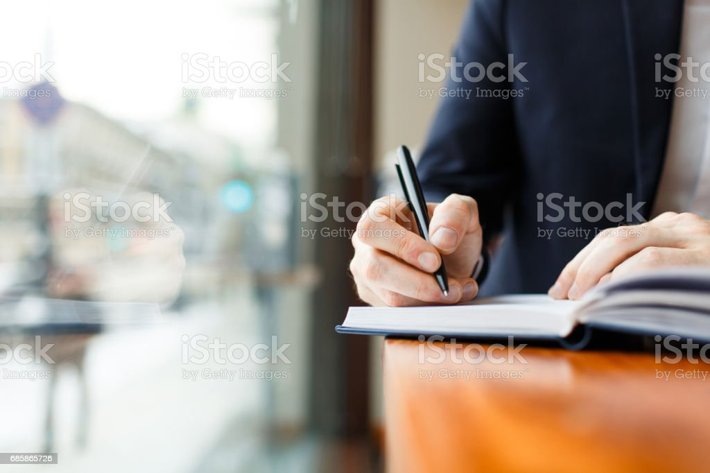 Businessman Writing in Planner at Cafe Window stock photo