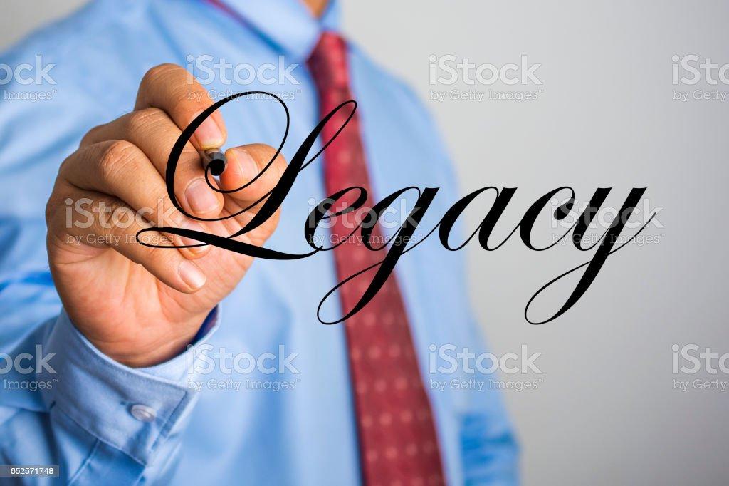 Businessman writing Legacy word on virtual screen. stock photo