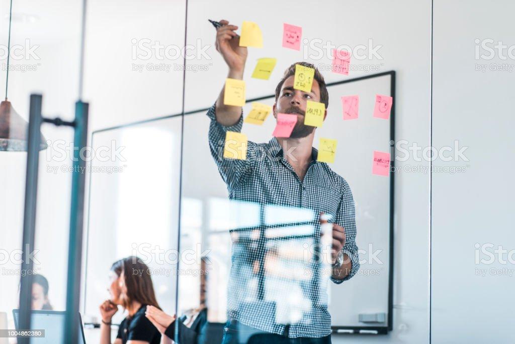 Unternehmer, die neue Ideen auf selbstklebende Notizen während eines Treffens im Büro zu schreiben – Foto