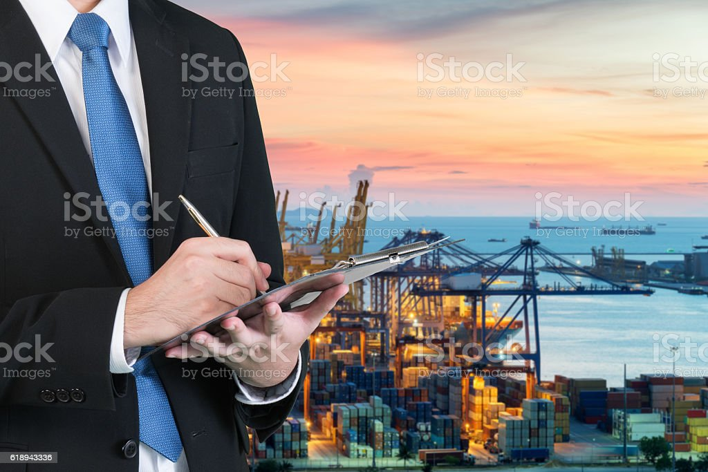 Businessman writing notebook for trading and logistics Businessman writing notebook for trading and logistics with blurred cargo container terminal at port in background. Business trading and logistics concept. Analyzing Stock Photo