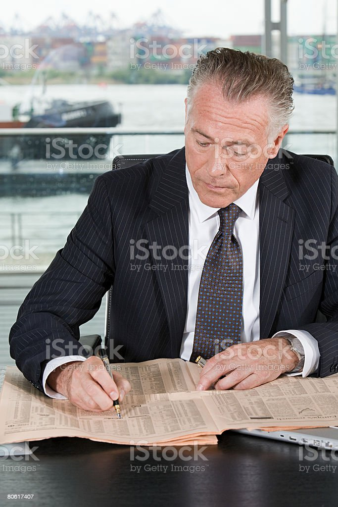 Businessman writing on a newspaper royalty-free stock photo