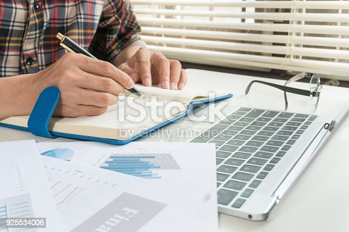 858031152istockphoto Businessman writing on notebook on wooden table, Concept finance planning and analyzes management. 925534006
