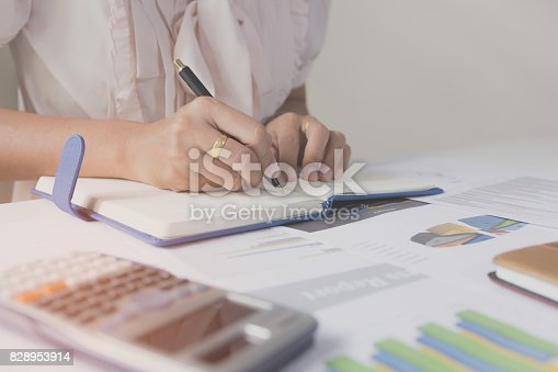 821678930 istock photo Businessman writing on notebook on wooden table, People are recording accounting data calculated from calculator. To report information to the CEO. Concept finance planing and analyzes management. 828953914